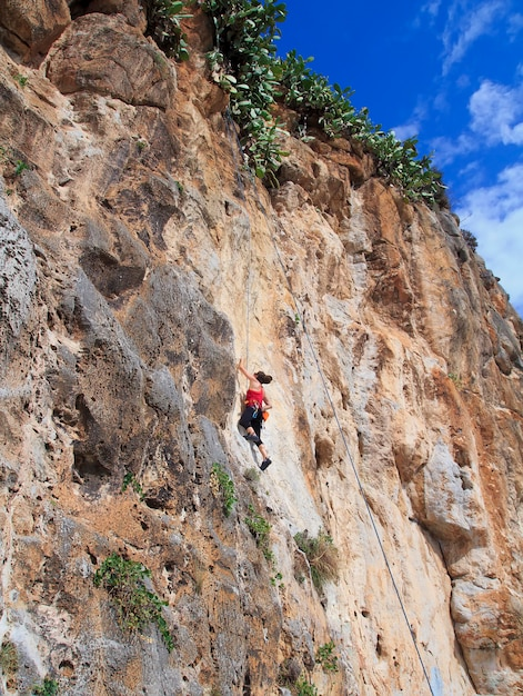 A young woman with a rope engaged in the sports of rock climbing on the rock. Premium Photo