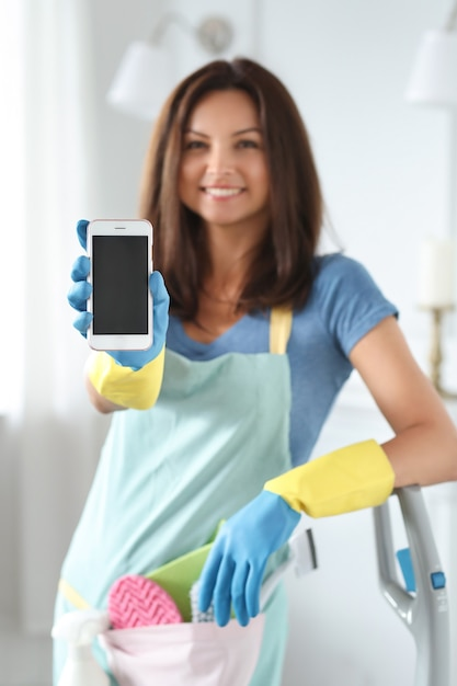 Young woman with rubber gloves showing smartphone Free Photo