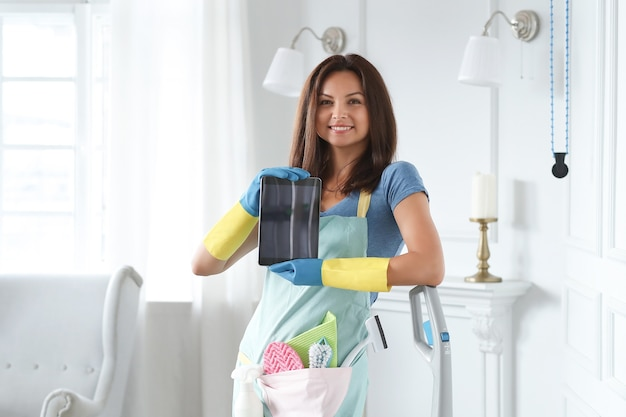 Young woman with rubber gloves showing tablet Free Photo