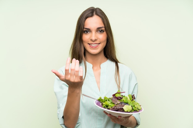 Young woman with salad inviting to come with hand. happy that you came Premium Photo