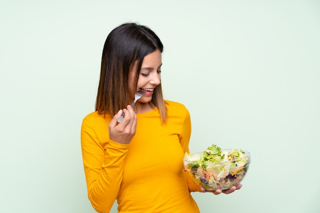 Young woman with salad over isolated green wall Premium Photo