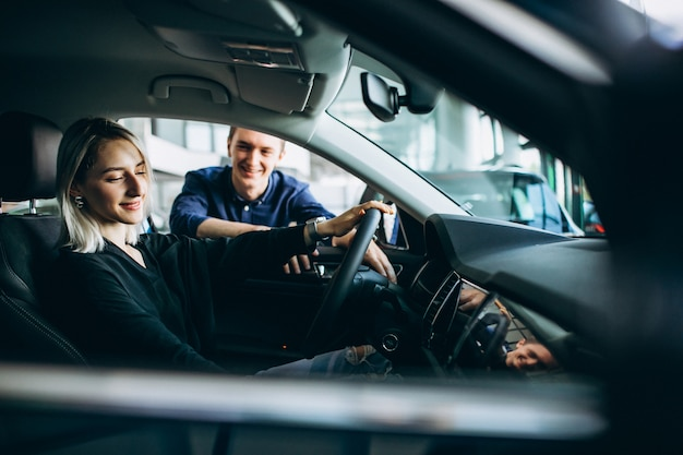 Young woman with salesman at a carshowroom Free Photo