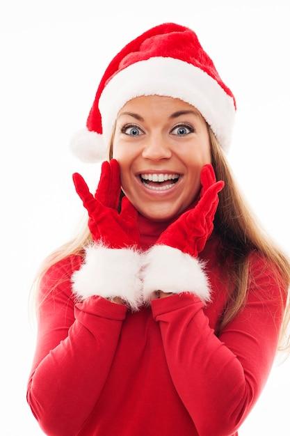 興奮しているように見えるサンタの帽子と手袋を持つ若い女性 無料写真