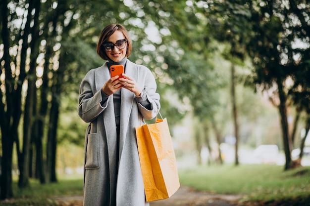 공원에서 쇼핑 가방을 가진 젊은 여자 무료 사진