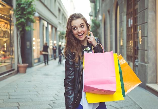 거리에서 쇼핑 가방을 가진 젊은 여자 프리미엄 사진
