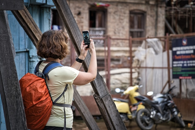 Young woman with short brunette hair photographing with her smartphone a hindu temple in nepal, asia. orange backpack with water proof cover Premium Photo