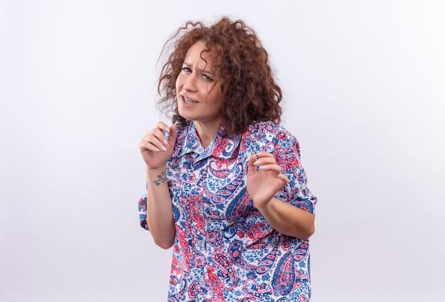 Giovane donna con capelli ricci corti in camicia colorata che fa gesto di difesa con le mani con espressione disgustata in piedi sopra il muro bianco Foto Gratuite