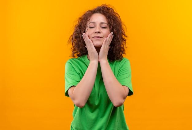 Giovane donna con i capelli ricci corti in maglietta verde, toccando il viso con le mani sensazione di emozioni positive in piedi sopra la parete arancione Foto Gratuite