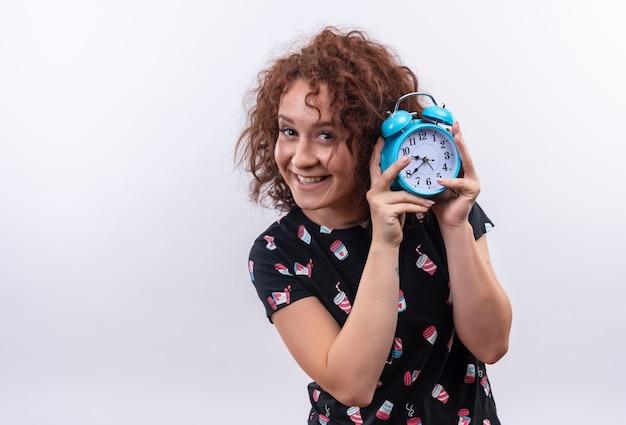 Молодая женщина с короткими вьющимися волосами держит будильник, весело улыбаясь, стоя над белой стеной Бесплатные Фотографии