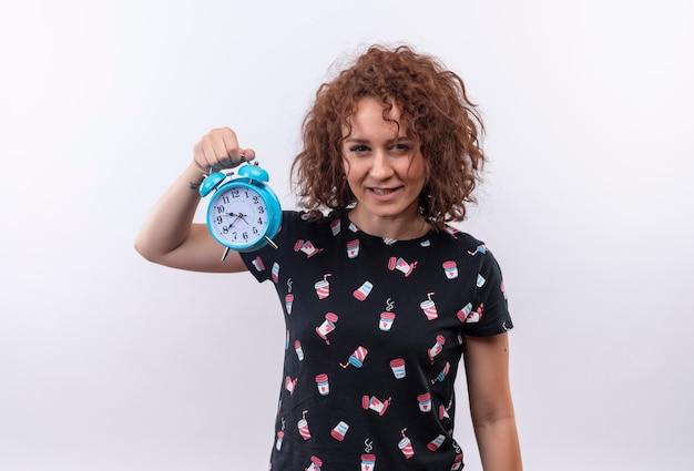 Молодая женщина с короткими вьющимися волосами держит будильник Бесплатные Фотографии