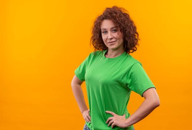 立っている顔に笑顔で自信を持って見える緑のtシャツの短い巻き毛の若い女性 無料写真