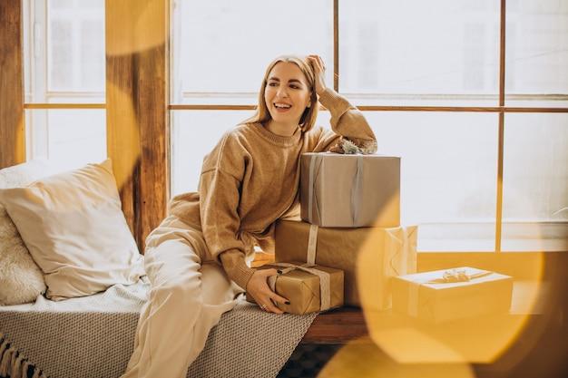크리스마스 선물 창가에 앉아 젊은 여자 무료 사진