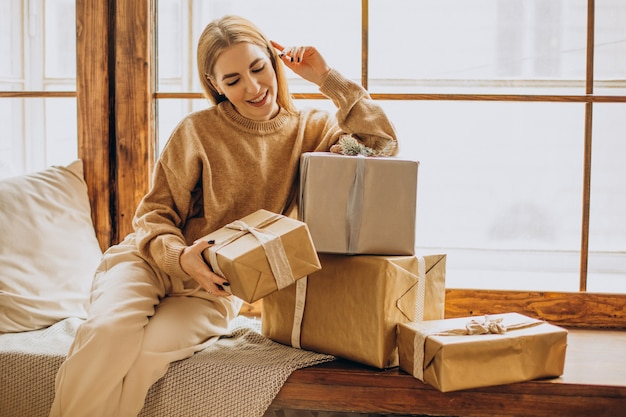 Young woman with sitting by the window with christmas gifts Free Photo