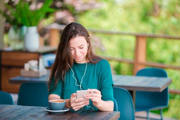 自由時間中にコーヒーショップで一人で座っている間スマートフォンを持つ若い女 Premium写真