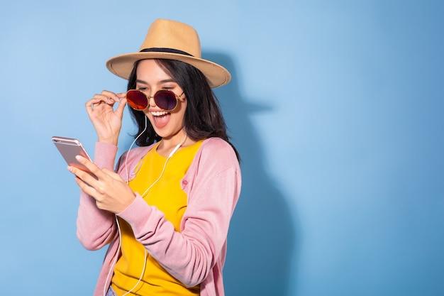 Молодая женщина со смартфоном и наушниками Premium Фотографии
