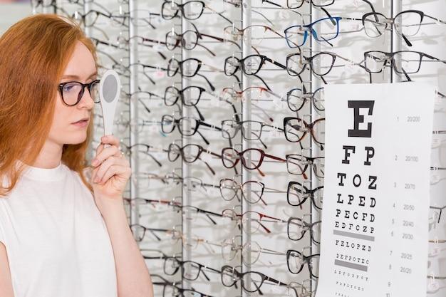 Молодая женщина в очках держит окклюдер перед своим глазом во время чтения диаграммы снеллена в офтальмологической клинике Бесплатные Фотографии