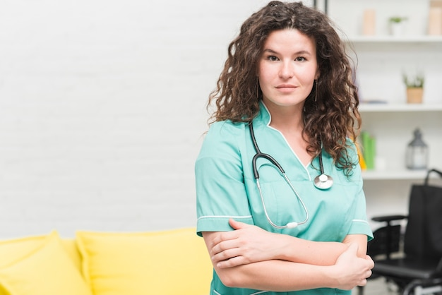 Young woman with stethoscope around her neck standing in hospital Free Photo