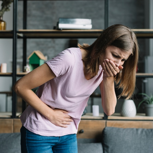 Young woman with stomach pain suffering from nausea Free Photo