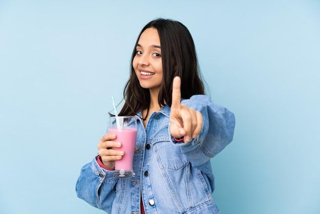 孤立した青い指を示して持ち上げてイチゴミルクセーキと若い女性 Premium写真