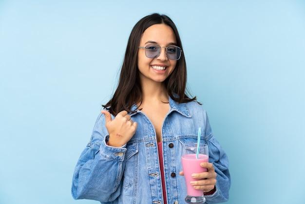 親指を立てるジェスチャーと笑顔で孤立した青にイチゴミルクセーキ Premium写真