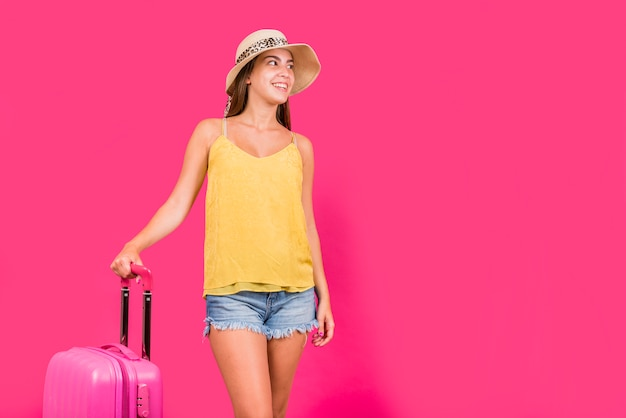 Young woman with suitcase on pink background Free Photo