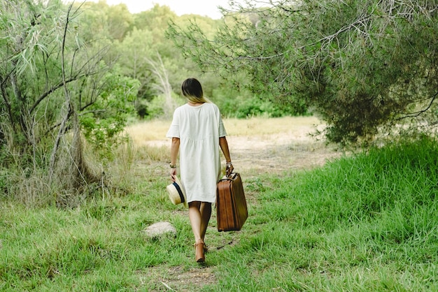 Young woman with suitcase and straw hat in the woods walking alone and sad. Premium Photo
