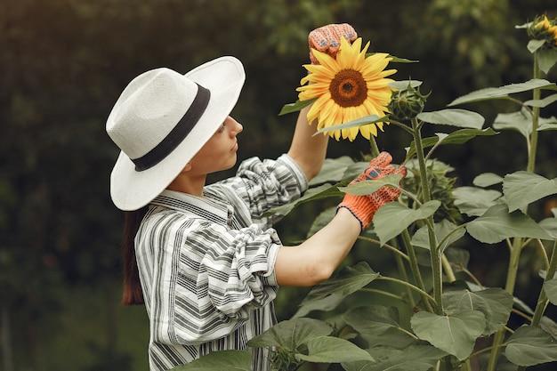 Молодая женщина с подсолнухами. дама в шляпе. девушка в саду. Бесплатные Фотографии