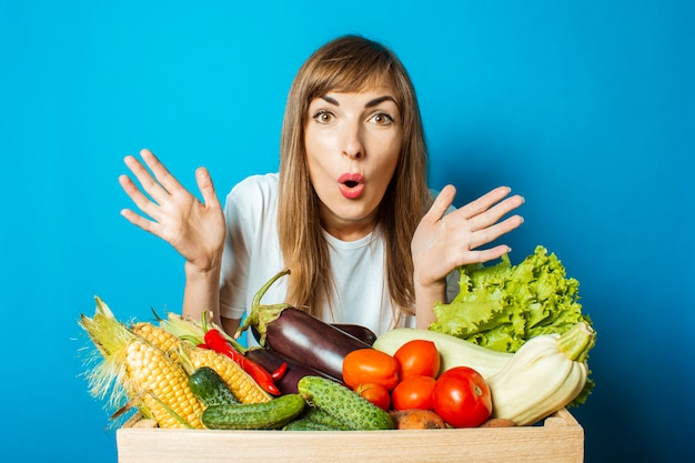 Young woman with a surprised face holds a box with fresh vegetables on blue. good harvest concept, natural product Premium Photo