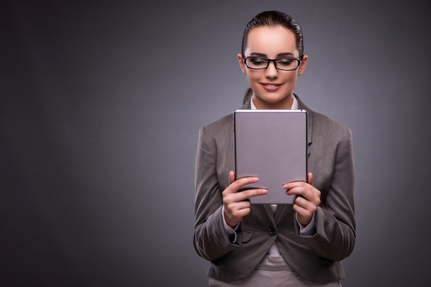 Young woman with tablet in business concept Premium Photo