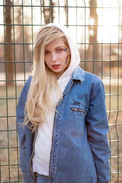 Young woman with temporary painted flowers on the face. teenage girl with long blond hair wear jeans jacket and hoody Premium Photo