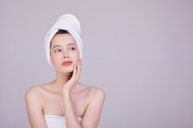 Young woman with a towel on her head, touches her face Premium Photo