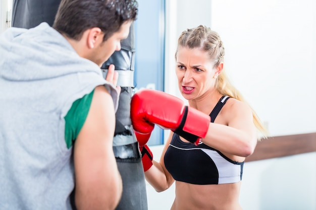 Young woman with trainer in boxing sparring Premium Photo