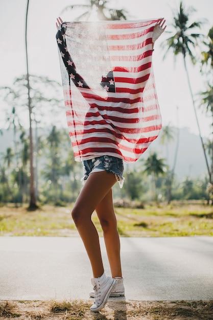 Giovane donna con bandiera usa in via tropicale Foto Gratuite