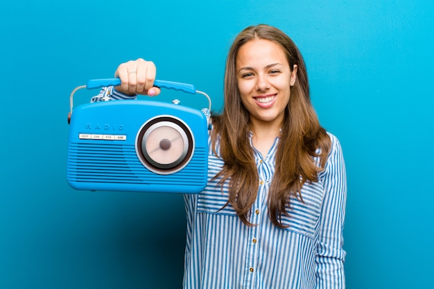 Young woman with a vintage radio on blue Premium Photo