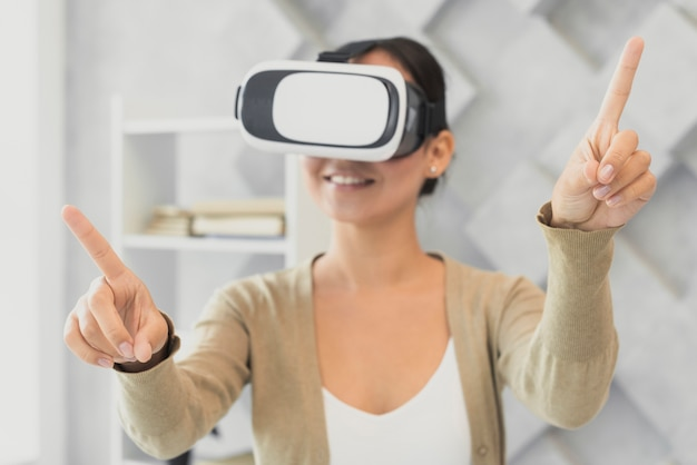 Young woman with virtual headset pointing Free Photo