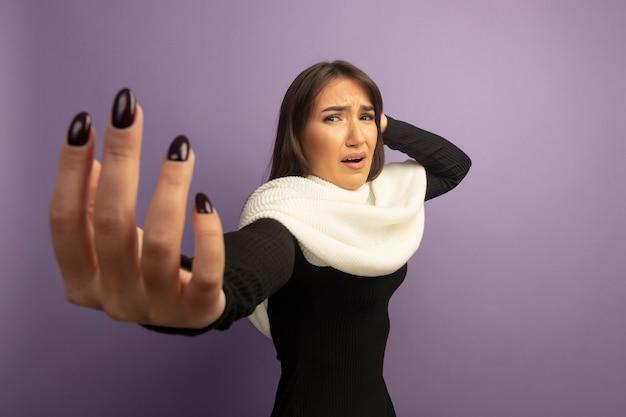 Giovane donna con sciarpa bianca confusa e molto ansiosa con il braccio fuori Foto Gratuite