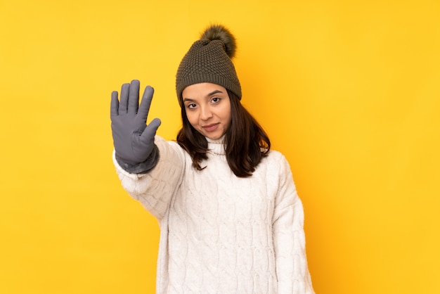 Young woman with winter hat over yellow wall counting five with fingers Premium Photo