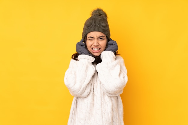 Young woman with winter hat over yellow wall frustrated and covering ears Premium Photo