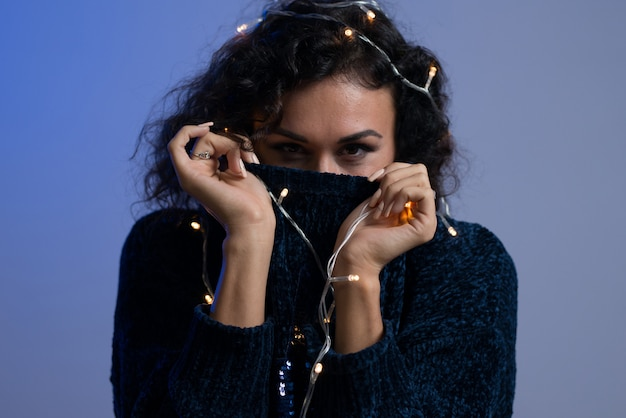 Young woman with xmas glowing lights celebration. Premium Photo