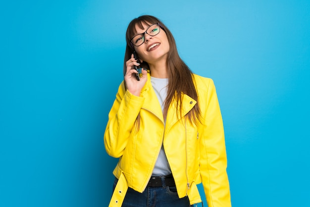 Young woman with yellow jacket on blue background keeping a conversation with the mobile phone Premium Photo
