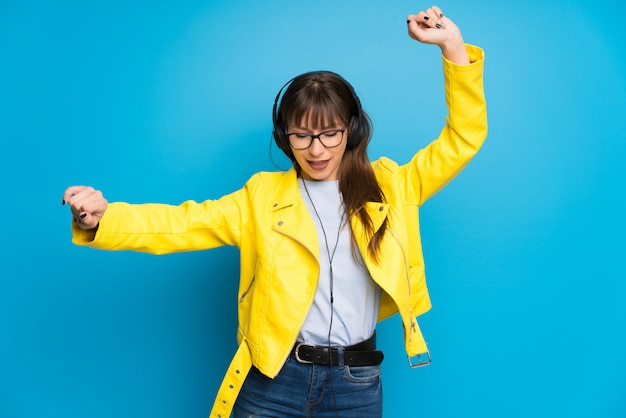 Young woman with yellow jacket on blue wall listening to music with headphones and dancing Premium Photo