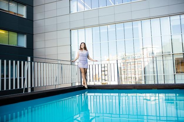 Giovane donna donna in un bellissimo abito di pizzo accanto alla piscina sul tetto Foto Gratuite