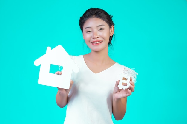 The young woman wore a white long-sleeved shirt with floral pattern, holding the house symbol and holding a currency symbol with a blue . Free Photo