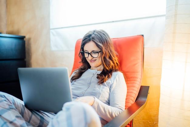 コンピューターと自宅のベッドから働く若い女性。 Premium写真