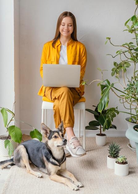 Giovane donna che lavora nel suo giardino di casa accanto al suo cane Foto Gratuite