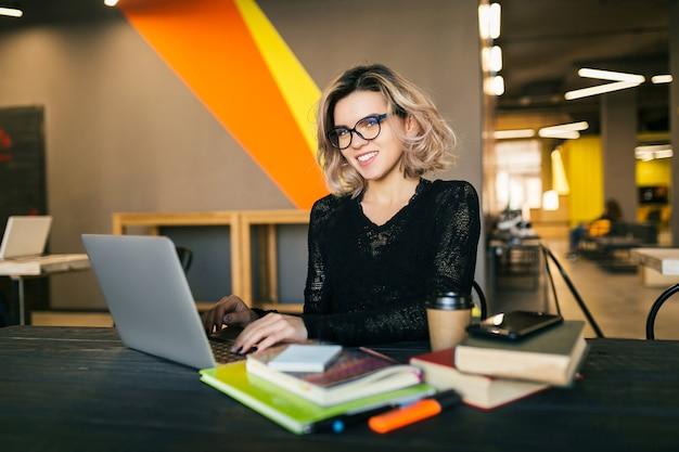 Giovane donna che lavora al computer portatile in ufficio di co-working Foto Gratuite