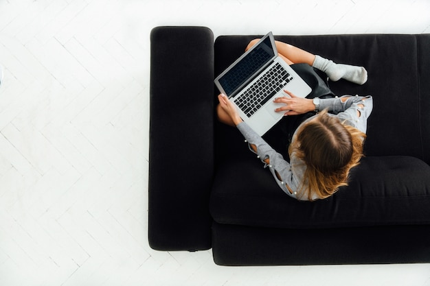 Young woman working on laptop, sitting on black cozy sofa, white floor. Free Photo