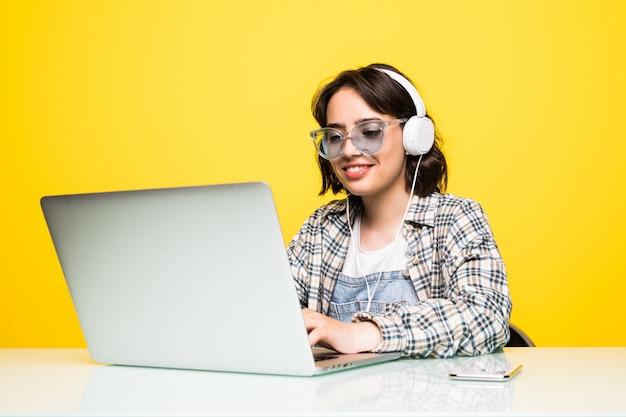 Молодая женщина, работающая на столе с изолированным ноутбуком Бесплатные Фотографии