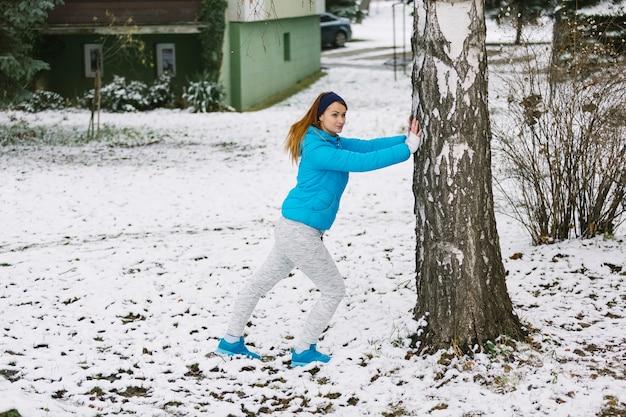 雪の多い風景の下で木の下で働く若い女性 無料写真