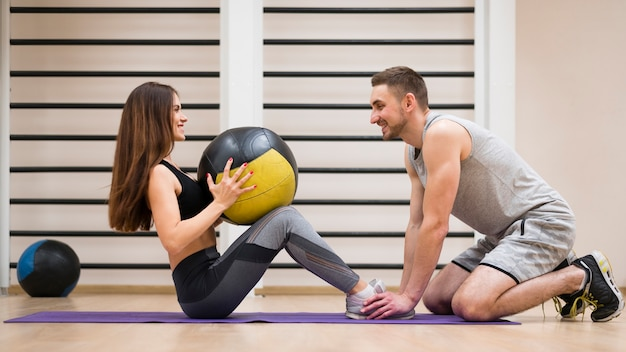 Young woman working out with her trainer Free Photo